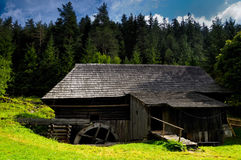 Watermill in countryside. Scenic view of traditional wooden watermill with forest in background Royalty Free Stock Photography