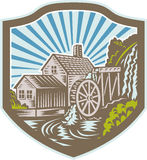 Watermill House Shield Retro. Illustration of a house with watermill falls river set inside shield with sunburst in the background done in retro woodcut style Royalty Free Stock Image