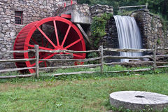 Watermill and millstone. Watermill with big red wheel, with old millstone nearby stock photo