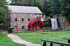 Watermill and millstone. Watermill with big red wheel, bridge and path royalty free stock images