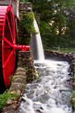 Watermill and millstone. Watermill with big red wheel, with water running stock photography