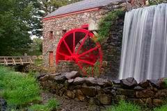 Watermill and millstone. Watermill with big red wheel, with water running stock image