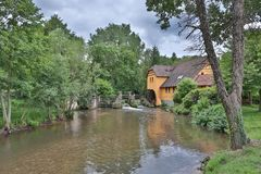 Watermill. This photo shows a watermill by a river in France Stock Photo