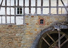 Watermill at stone wall of old house Royalty Free Stock Images