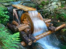 Watermill on stream. Wooden watermill on cascading stream or river Royalty Free Stock Photo