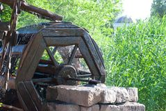 Watermill wooden water wheel mill, stone bricks wall, water flows from the wheel, on the background of green trees. Park summer rest weekend royalty free stock image