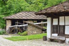 Watermolen, een oud huis en een houten bank in Etara, Bulgarije Stock Fotografie