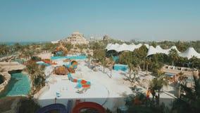 Waterpark en Dubai en día de verano, las atracciones y las diversiones, gente están descansando metrajes