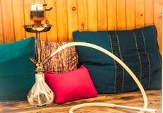 Waterpijp onder de gekleurde kussens op het hout Royalty-vrije Stock Foto's