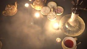 Waterpijp op de bovenkantmening van de glaslijst van koppenkaars en smartphone oostelijke theeceremonie Modieuze oosterse shisha  stock videobeelden