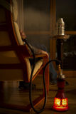 Waterpipe. Man smoking waterpipe at home Royalty Free Stock Photos