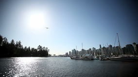 Waterplane flyover marina. Waterplane flying through the sun over the Vancouver False Creek Marina near Stanley Park stock footage