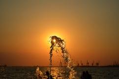 Waterplons op de achtergrond van zonsondergangkleuren met mensen en kranensilhouetten Royalty-vrije Stock Fotografie