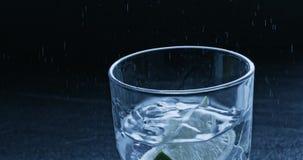 Waterplonsen uit het glas van een dalend stuk van kalk De langzame motie2k video shooted op 240 fps stock footage