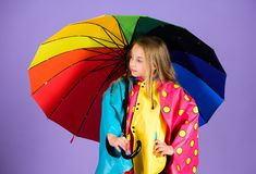 Waterproof accessories for children. Waterproof accessories make rainy day cheerful and pleasant. Kid girl happy hold. Colorful umbrella wear waterproof cloak royalty free stock photo