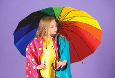 Waterproof accessories for children. Waterproof accessories make rainy day cheerful and pleasant. Kid girl happy hold. Colorful umbrella wear waterproof cloak stock photo