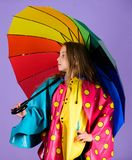 Waterproof accessories make rainy day cheerful and pleasant. Kid girl happy hold colorful umbrella wear waterproof cloak. Enjoy rainy weather with proper stock photos