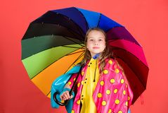 Waterproof accessories make rainy day cheerful and pleasant. Kid girl happy hold colorful umbrella wear waterproof cloak. Enjoy rainy weather with proper stock images