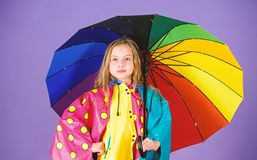 Waterproof accessories make rainy day cheerful and pleasant. Kid girl happy hold colorful umbrella wear waterproof cloak. Waterproof accessories for children royalty free stock photos