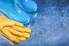 Waterproof gumboots leather gloves on metallic background garden Stock Photography