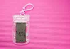 Free Waterproof Mobile Phone Case With Water Droplets  On Pink Mat Background. Plastic PVC Waterproof Case For Smartphone, Zip Stock Photo - 144876630