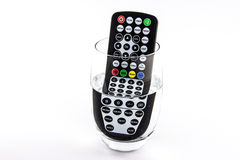 Waterproof TV remote control in a glass of water Royalty Free Stock Photo