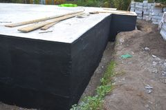 Waterproofing foundation bitumen. Foundation Waterproofing, Damp proofing Coatings. Waterproofing house foundation with spray on tar. Construction techniques Stock Photo