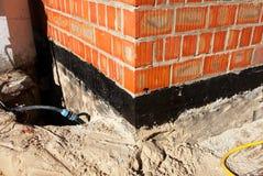 Waterproofing fundamentbitumen Fundament som Waterproofing, fuktiga provkopieringsbeläggningar Waterproofing husfundament med spr Royaltyfri Fotografi