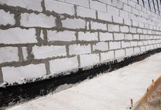 Waterproofing and insulationhouse  foundation wall. Waterproofing house foundation with bitumen membrane. Waterproofing new foundation wall. Waterproofing house Royalty Free Stock Photo