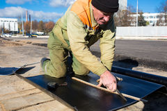 Waterproofing works with roll roofing felt. Construction worker cutting roll roofing felt Royalty Free Stock Image