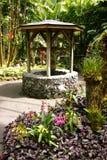Waterput in een tuin stock afbeeldingen