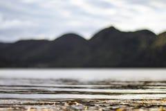 Waterrimpelingen op kust met bergen in afstand De zachte golven van het meerstrand stock afbeelding