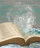 Waters of bible truth. Photo of crashing wave on open bible pages depicting refreshing waters of bible truth royalty free stock photo