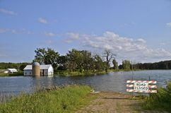 Waters flood road and barn Royalty Free Stock Images