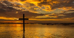 Waters of Salvation. Dark cross on a beach with a wonderful sunset sky stock photography