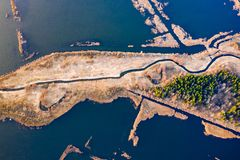 Waters surrounding dry piece of land, aerial view. Beautiful rural landscape. Aerial scenery royalty free stock photos