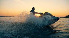 Waterscape de la puesta del sol con un hombre adulto que conduce un waverunner almacen de metraje de vídeo
