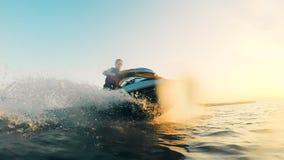 Waterscape escénico con un hombre en un esquí del jet, vehículo del waverunner en luz del sol almacen de metraje de vídeo