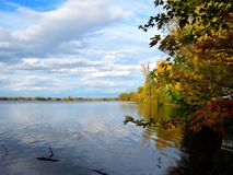 Waterscape in the fall with blue sky and white clouds. By the river royalty free stock photo