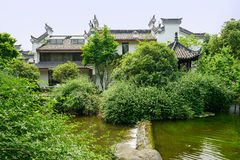 Waterside Chinese traditional houses in woods on sunny summer da Royalty Free Stock Image
