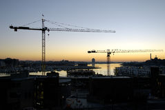 Waterside Development. View of harbor development and construction during early morning with two cranes Stock Photos