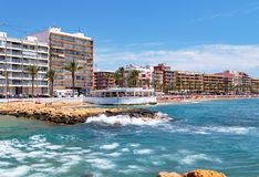 Waterside distant view Playa del Cura beach, urban skyline typical high rise houses coastal restaurant building. Palm tree lined promenade. Lot of people royalty free stock photography