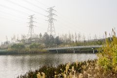 Waterside grass,fenced footbridge and electricity pylons in sunny winter afternoon. Waterside grass,electricity pylons and fenced footbridge in sunny winter royalty free stock image