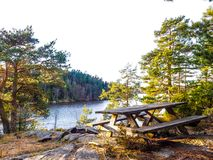 Waterside picnic bench. Wooden picnic bench on a plateau at a forest clearing, overlooking a waterway Royalty Free Stock Images