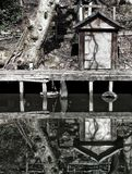 A waterside run down wooden jetty with a small shack and tree reflected in the still water stock photography
