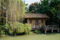 Waterside thatched house in trees and shrubs on sunny day Royalty Free Stock Images