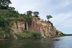 Waterside Victoria Nile scenery in Uganda. Waterside scenery showing the Victoria Nile with a big overgrown rock formation in Uganda (Africa Stock Photography