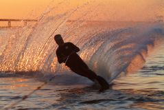 Waterskiing at sunrise. A man water skiing at sunrise Royalty Free Stock Photos
