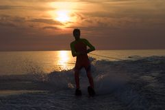 Waterskiing at sunset. Man waterskiing on ocean silhouetted with orange sunset Stock Photos