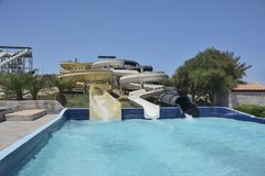 Waterslides and pipe in aquapark in the open air, in the bright summer sunny day stock images